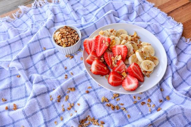 Fragole fresche con fetta di banana sul piatto bianco su un tavolo di legno.