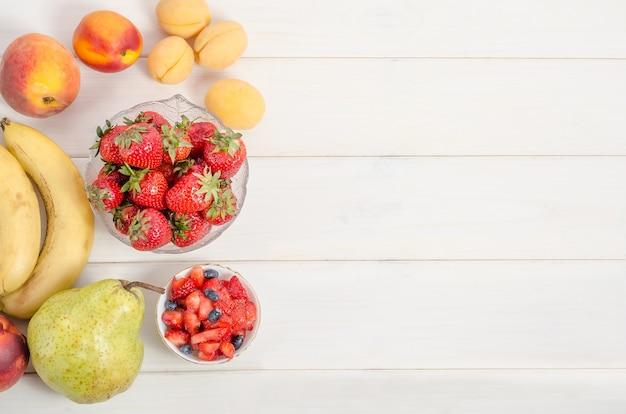 Fragole fresche con frutti su un fondo di legno bianco con lo spazio della copia. ingredienti per macedonia di frutta.