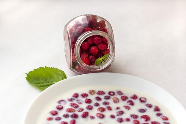 Fragole fresche con latte in una ciotola bianca e vaso di vetro con frutti di bosco.