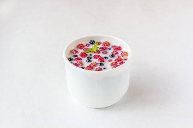 Fragole fresche con latte in una tazza bianca.