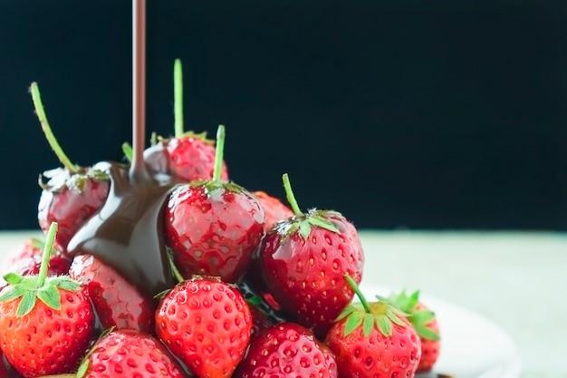 Fragole fresche con versare cioccolato fondente su sfondo nero