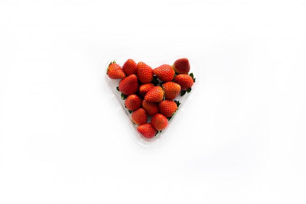 Fragole fresche succose in una scatola a forma di cuore