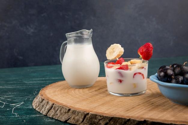 Fragole in crema servite con latte e ciliegie su un piatto di legno