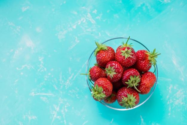 Fragole mature fresche in ciotola isolata su fondo blu molle. fragole appena raccolte sul tavolo color smeraldo. stile di vita sano con frutta. copia spazio