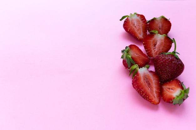 Fragole mature rosse fresche sul copyspace rosa di vista superiore del fondo
