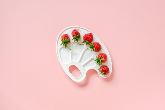 Fragole mature rosse su una tavolozza artistica su fondo rosa con lo spazio della copia.