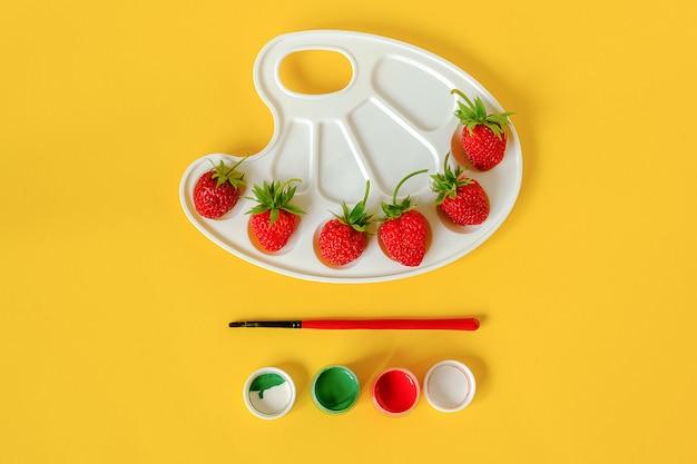 Fragole mature rosse su una tavolozza, su una spazzola e su una gouache artistiche su giallo