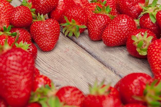 Fragole mature rosse sulla fine di legno della tavola su