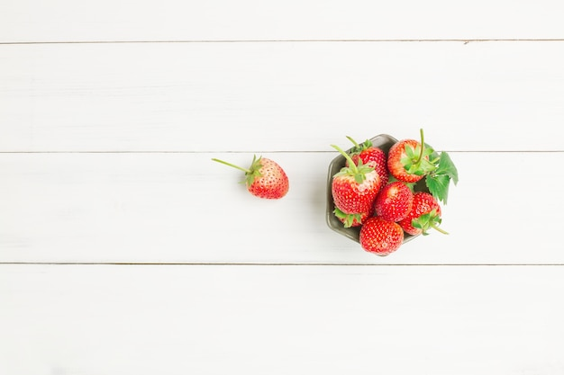 Fragole rosse fresche in tazza di ceramica della ciotola sul pavimento di legno bianco della plancia per fondo.