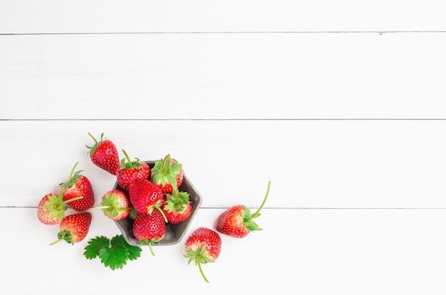 Fragole rosse fresche in una tazza di ceramica della ciotola sul pavimento di legno bianco della plancia per fondo.