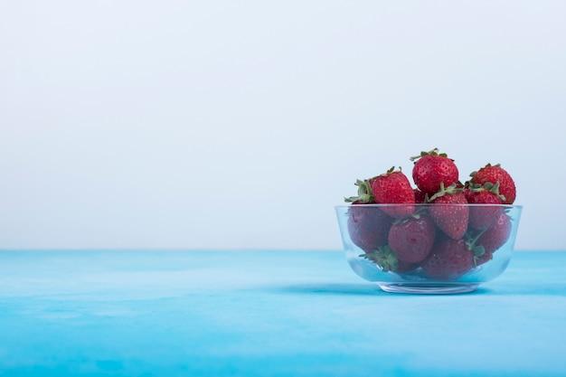 Fragole rosse in una tazza di vetro sull'azzurro, vista di angolo.