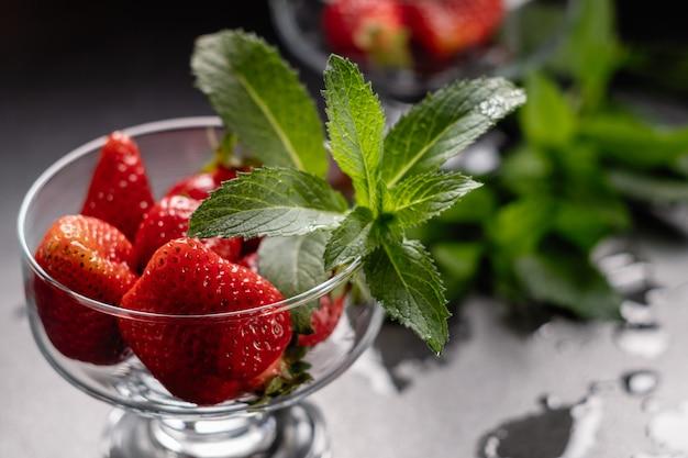 Fragole rosse mature fresche in una ciotola di vetro sul nero
