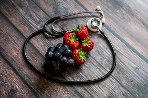 Fragole rosse scozzesi e uva nera con lo stetoscopio sulla parte superiore del tavolo in legno