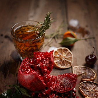 Fragrante tè alla frutta con mandarini, limoni essiccati e rosmarino su un tavolo di legno. stile country.