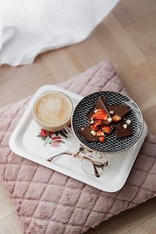 Fragranti cioccolato fondente con fragole servite con caffè su un cuscino rosa