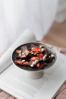 Fragranza al cioccolato fondente con fragole secche in un piatto su un libro aperto