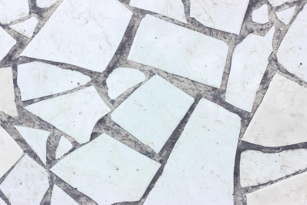 Frammenti di ceramica colorata e pavimento in cemento