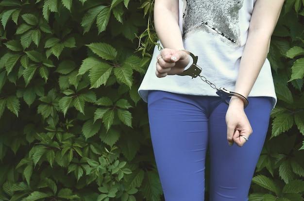 Frammento del corpo di una ragazza giovane criminale con le mani in manette contro un'edera fioritura verde