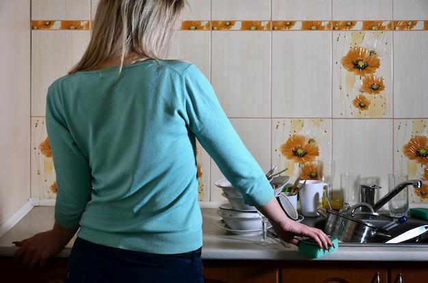 Frammento del corpo femminile al bancone della cucina, pieno di