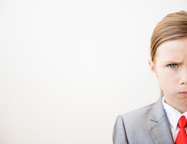 Frammento del volto di un bambino in giacca e cravatta e cravatta rossa su sfondo bianco