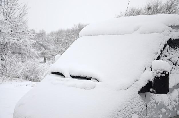 Frammento dell'auto sotto uno strato di neve dopo una fitta nevicata. il corpo dell'auto è coperto di neve bianca