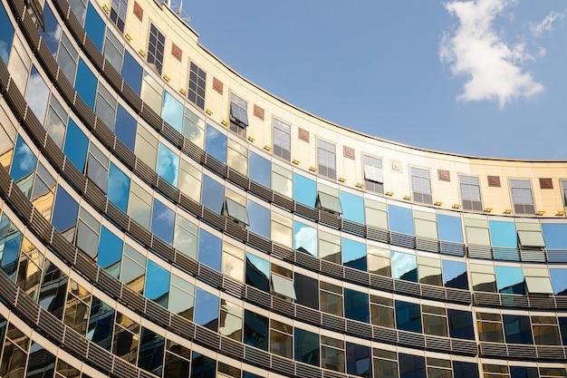 Frammento di insolito semicerchio che bulding con pareti di vetro di colori blu e dorati