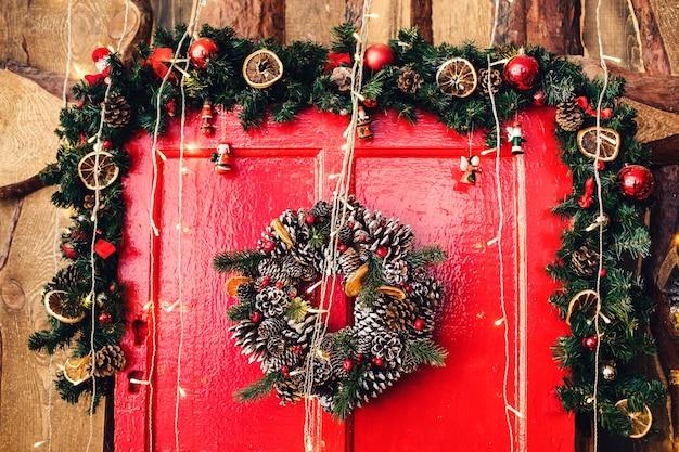 Frammento di porta di legno rossa con decorazioni natalizie.