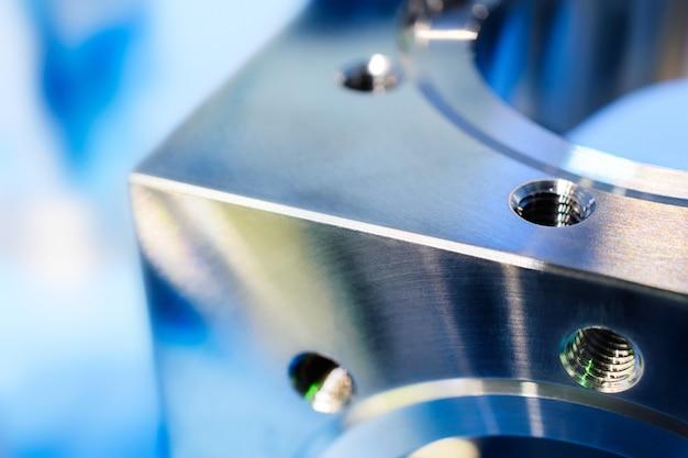Frammento di un cubo di metallo con fori e filettatura metrica.