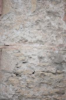 Frammento di vecchia struttura grungy con vernice scheggiata e crepe o superficie grigia del cemento e del muro di cemento