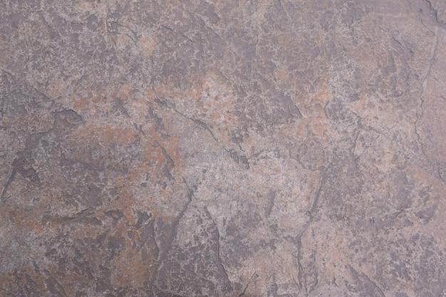 Frammento stagionato del muro di crepa del vecchio cemento, struttura concreta incrinata del pavimento