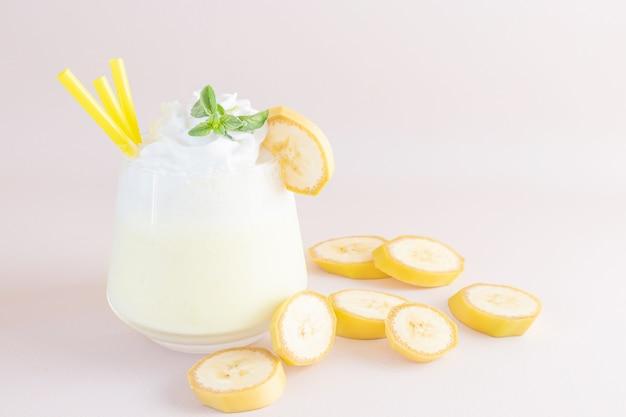 Frappè alla banana in vetro trasparente. nelle vicinanze ci sono fette di banana. il concetto di deliziose bevande fresche, cibi sani per colazione e spuntini.