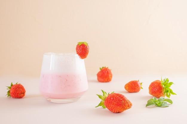Frappè alla fragola in un bicchiere trasparente. intorno - fragole. il concetto di deliziose bevande fresche, cibi sani per colazione e merenda.