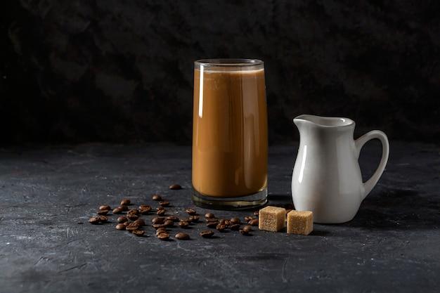 Frappe caffè freddo in vetro alto. bevanda estiva fresca su uno sfondo scuro in chiave di basso.