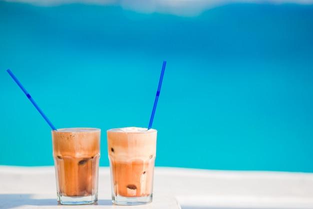 Frappe, caffè freddo sulla spiaggia. frappuccino, frappe o latte ghiacciato del caffè di estate in un fondo di vetro alto il mare nel bar della spiaggia
