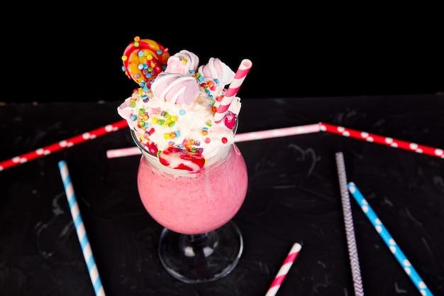 Frappè rosa estremo con bacche, lamponi, fragole, caramelle marshmallow