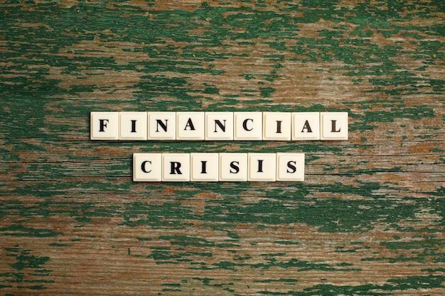 Frase crisi finanziaria fatta di stampatello in plastica sul vecchio backgraund in legno
