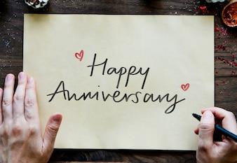 Frase felice anniversario su una carta