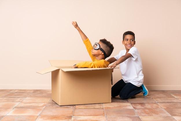 Fratelli afroamericani che giocano. ragazzo all'interno di una scatola di cartone con occhiali da aviatore