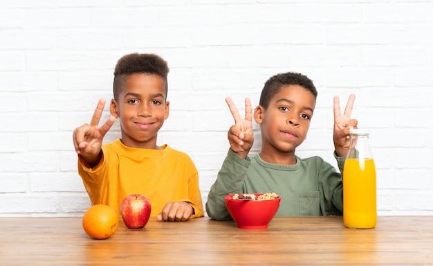 Fratelli afroamericani facendo colazione e facendo il gesto di vittoria