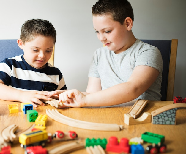 Fratelli che giocano con blocchi, treni e automobili