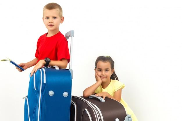 Fratelli e sorelle adorabili con una valigia che si siede mentre viaggiano