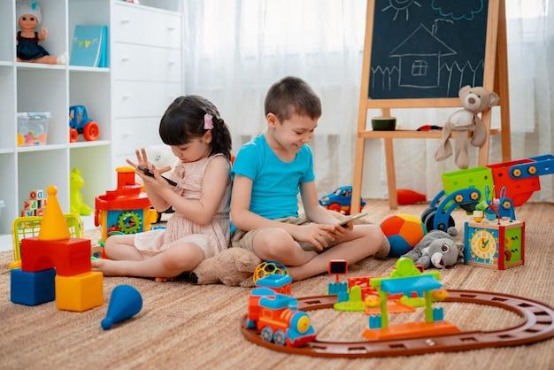 Fratelli e sorelle, fratelli e sorelle, gli amici si siedono nella sala giochi per bambini della casa al piano terra con gli smartphone, staccati dai giocattoli sparsi.