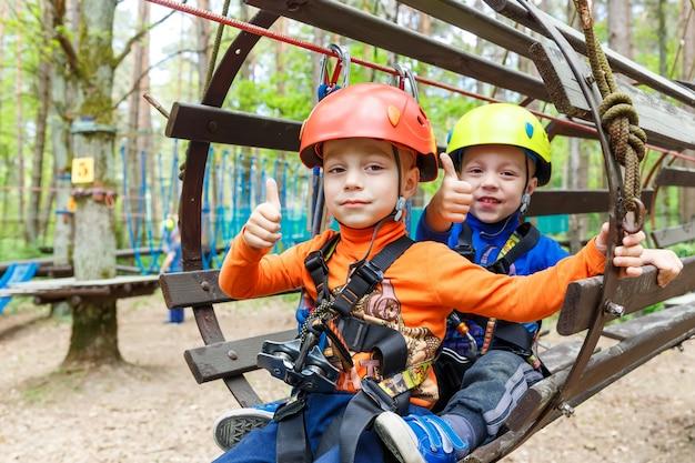 Fratelli gemelli che indossano casco e arrampicata
