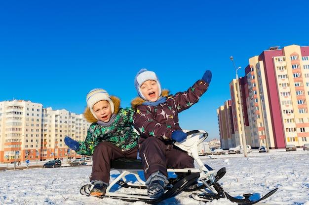 Fratelli gemelli che posano sul motorino della neve
