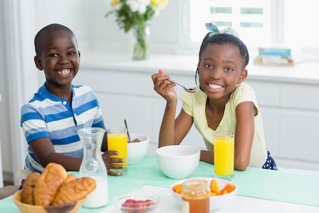 Fratelli germani che mangiano prima colazione sul tavolo da pranzo a casa