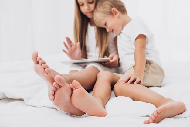Fratelli vista frontale stare a letto mentre guardando il loro tablet