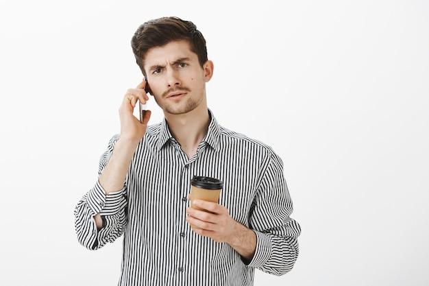 Fratello barbuto caucasico rigoroso serio in camicia a righe, che tiene tazza di caffè e parla al telefono con espressione concentrata, sentendosi intensamente discutendo importante incontro di lavoro sul muro grigio