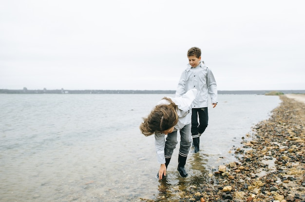 Fratello con sorella si diverte in mare indossando l'impermeabile