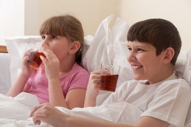 Fratello e sorella che bevono tè seduti a letto. ambientazione interna. avvicinamento.