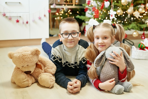 Fratello e sorella che si siedono vicino all'albero di natale con i peluche